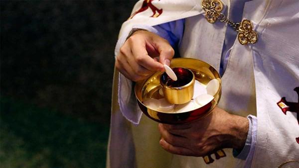 Католический священник со Святыми Дарами (Телом и Кровью Христа)